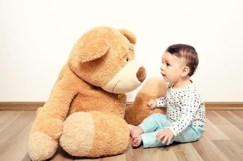 Beautiful innocent newborn speaking with his best friend, teddy